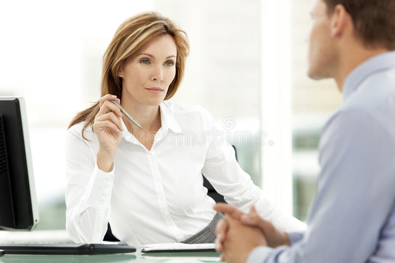 Business interview. Beautiful female business executive listening to a businessman at an interview in her office royalty free stock images