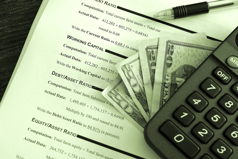 Business investment. Calculator, pen and money on top of a business financial worksheet-image done with a green tint royalty free stock images
