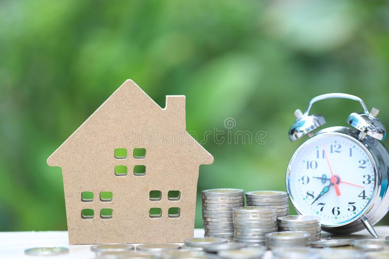 Business investment and real estate, Stack of coins money and Model house on natural green background, Saving for prepare in. Future stock photo