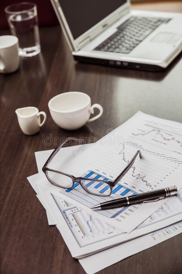 Business items sunglasses graphics documents and laptop on the tabless meeting in the office. Business negotiations in the office Business items sunglasses royalty free stock photography