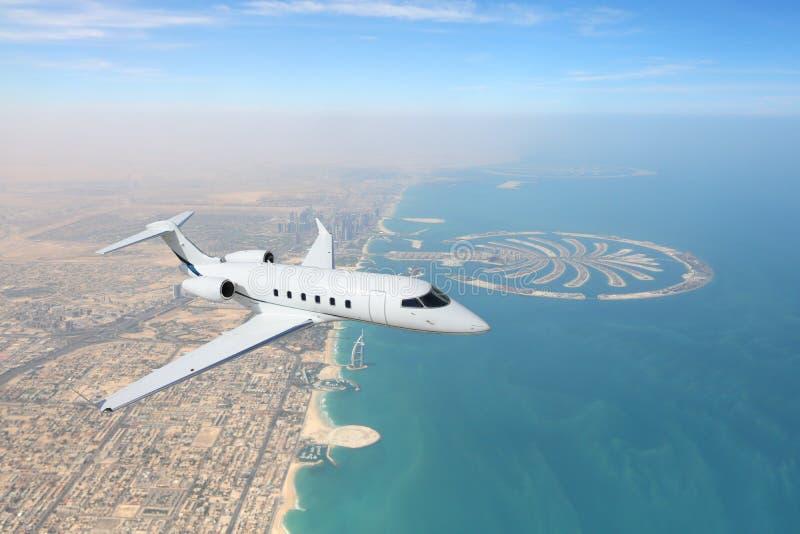 Business jet airplane flying over Dubai city and sea coastline stock photography