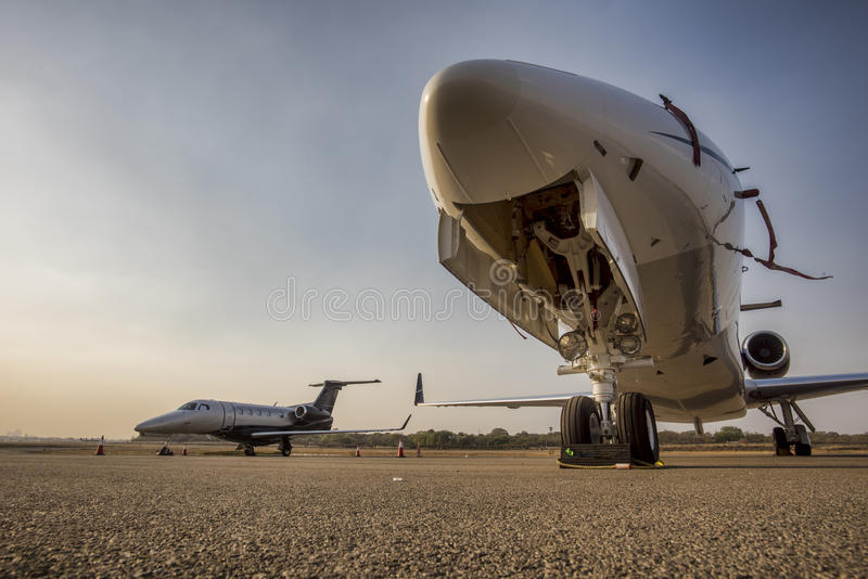 Business jets. Silver business jet with nose wheel and hydraulics in closeup with undercarriage doors wide open. A second similar jet plane is parked on the stock photography