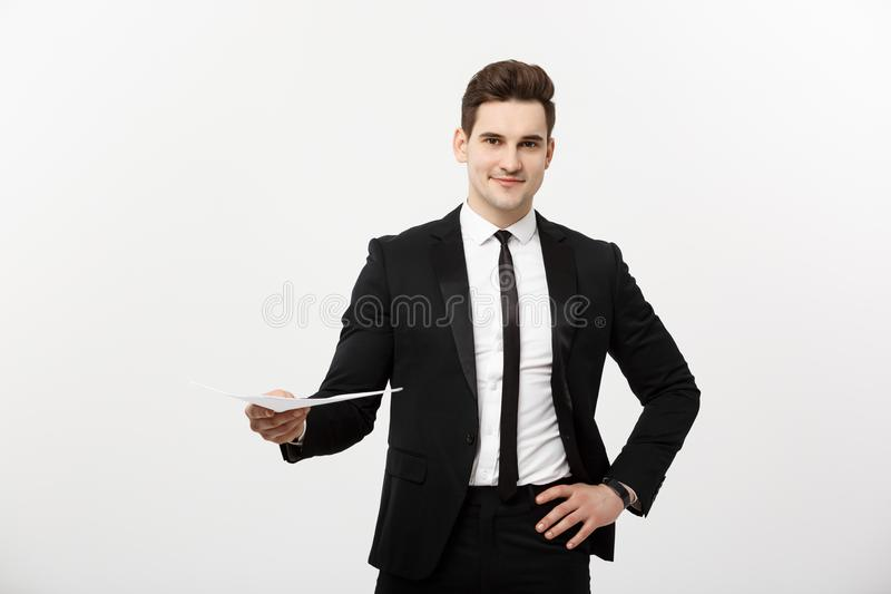Business and Job Concept: Elegant man in the suit holding resume for job hiring in the bright white interior. stock image