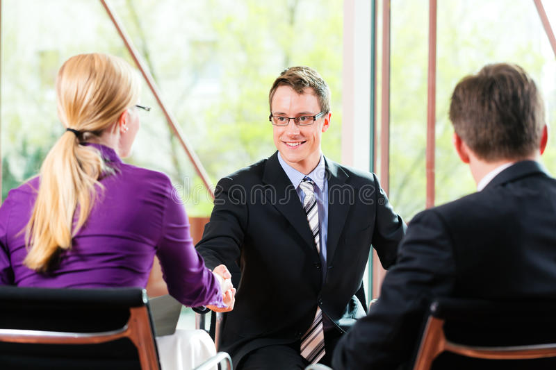 Business - Job Interview with HR and applicant. Business - young man as applicant sitting in job interview with future boss and HR stock images