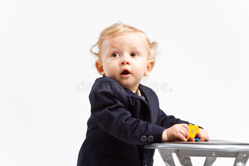 Business kid. Dressed in office outfit next to a small chair royalty free stock images
