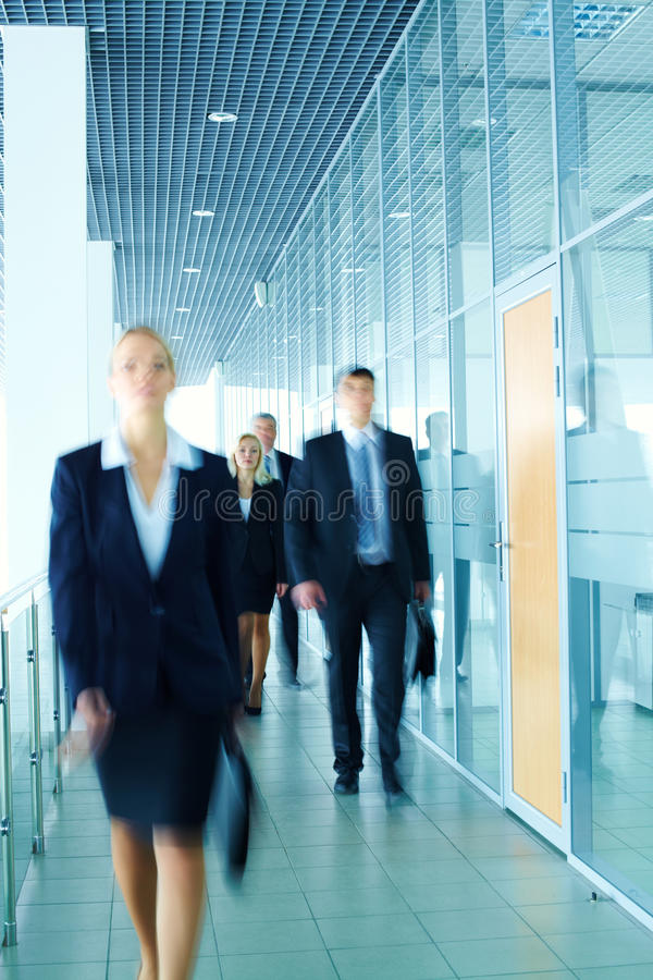 Business lady. Walking along the corridor ahead of her colleagues royalty free stock photos