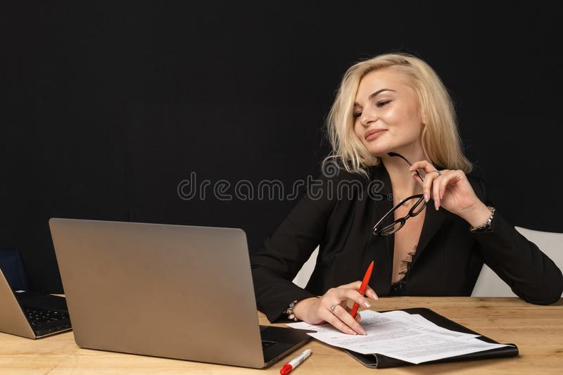 Business lady beautiful blonde woman intelligent managing director. Sitting in modern office. Female economist is analyzing the activities of company via net royalty free stock images
