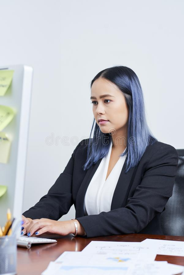 Business lady concentrated on work. Young Asian businesswoman with blue hair concentrated on working on computer royalty free stock photo