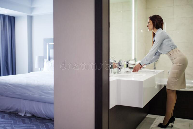 Pretty female in formal wear looking at mirror while washing hands in bathroom. Business lady in dressed in button-down shirt, pencil skirt and stilettos stock photography