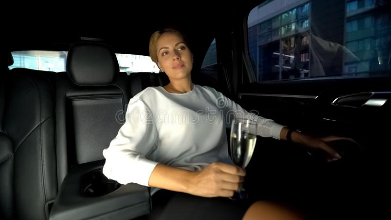 Business lady drinking champagne sitting on backseat, driving home with driver stock images