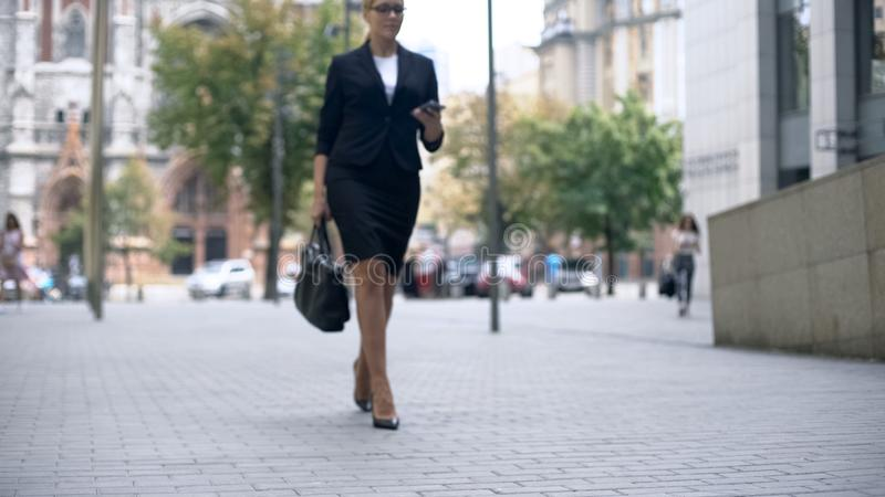 Business lady in elegant suit walking to work, successful career, busy lifestyle stock image