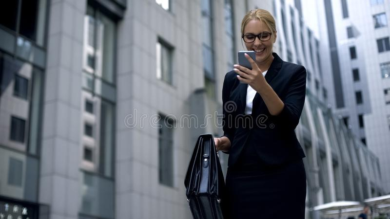 Business lady excited about good news from phone, successful deal, promotion. Stock photo royalty free stock image
