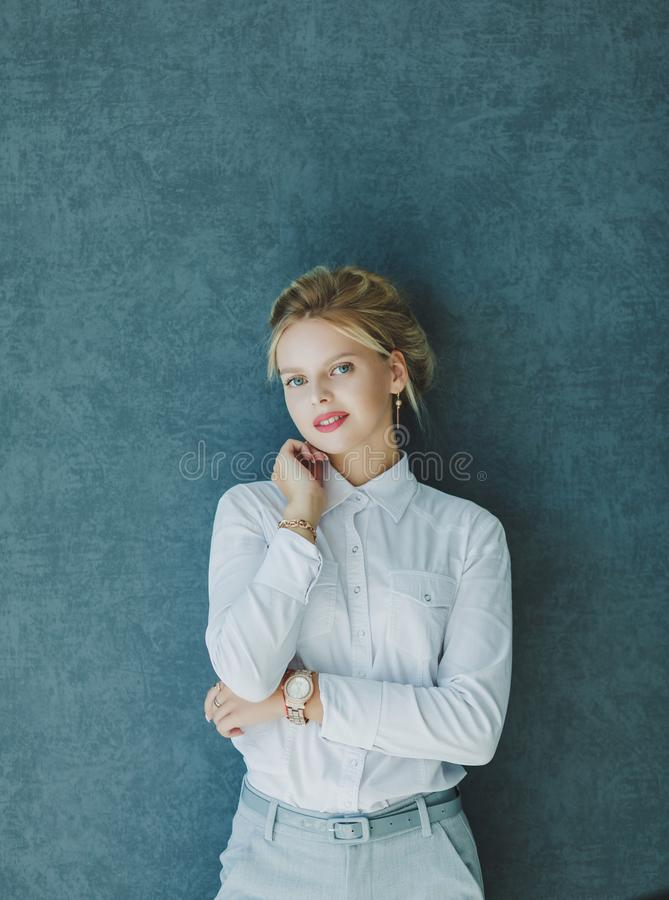 Business lady in formal wear. Portrait of a business lady in formal wear near the wall stock image