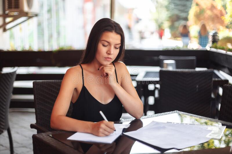Business lady girl sits at a table in a cafe, considers paper, thinks. Resume, signing an important business deal. Work. Away from home stock photography