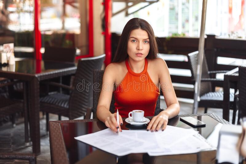 Business lady girl sits at a table in a cafe, considers paper, thinks. Resume, signing an important business deal. Work. Away from home royalty free stock image