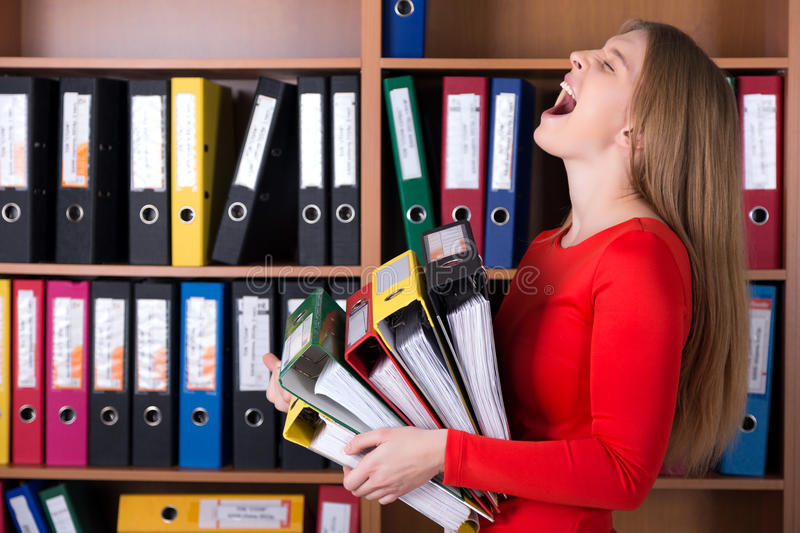 Business Lady holding large Stack of Office Folders. Casual Clothing Dress Code young beautiful face Cupboard with many Documents Files of different colors royalty free stock photography