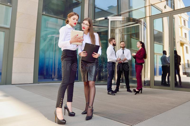 Business lady. Office staff. Two young girls with electronic tab stock photo
