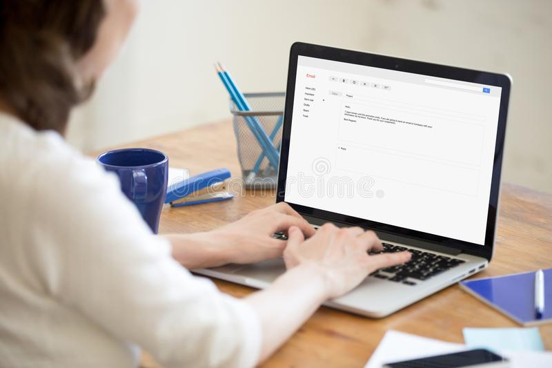 Business lady in office typing reply to corporate email. Business lady in office types reply to corporate email. Entrepreneur responds to message about stock image