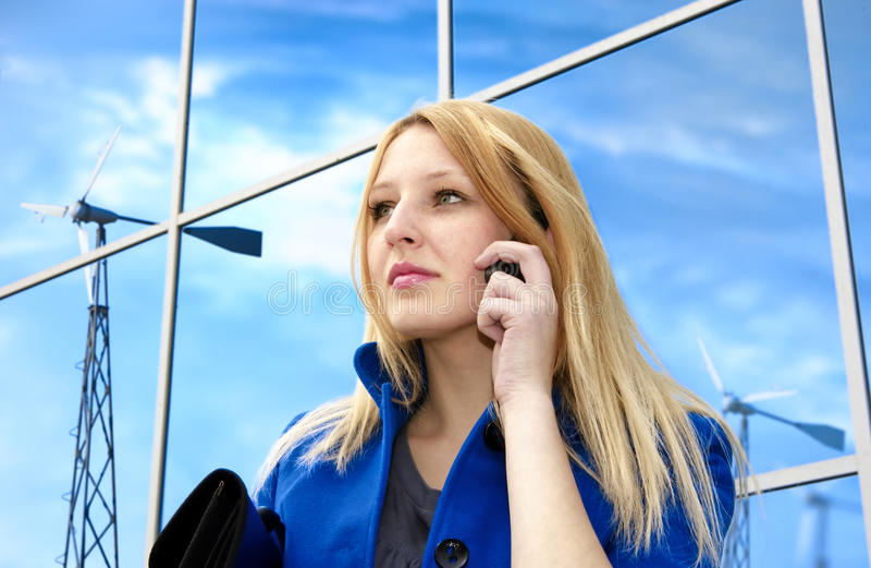 Business lady with phone near windgenerators royalty free stock photo