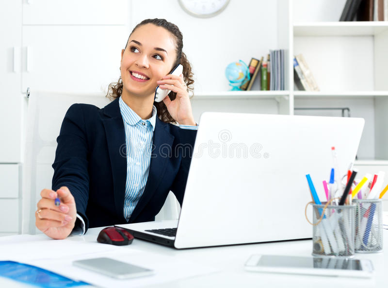 Business lady with smart phone and laptop. Cheerful business lady with smart phone and laptop in office royalty free stock photography