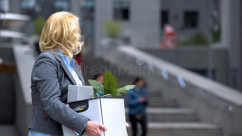 Business lady with stuff box looking at office building, pension unemployment royalty free stock images