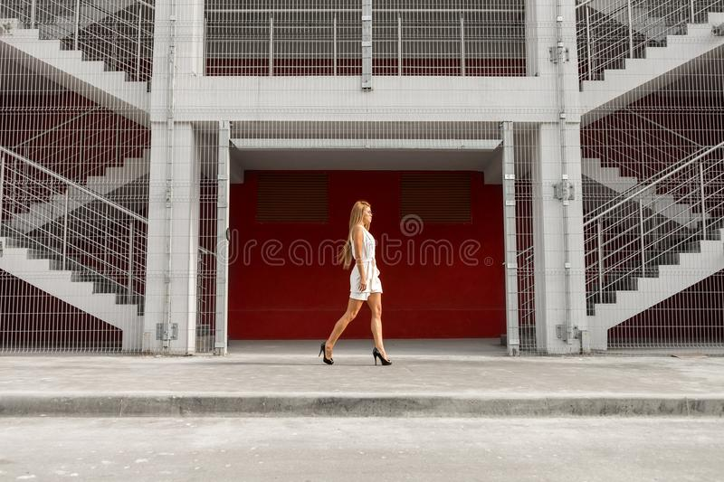 Business lady urban lifestyle. Fashion portrait of beautiful young business woman in white vogue suit against industrial red wall. Urban style girl, quick stock photos
