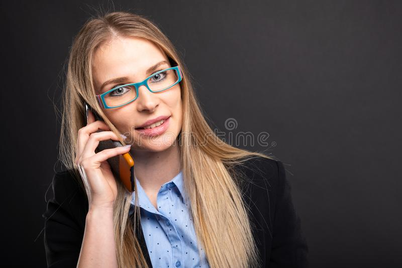 Business lady wearing blue glasses talking at smartphone stock image