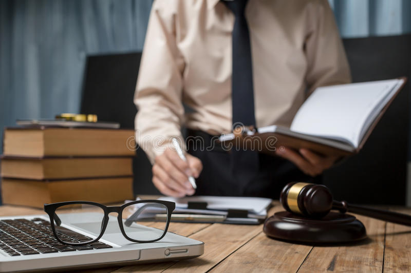 Business lawyer working hard at office desk workplace with book. And documents stock photo