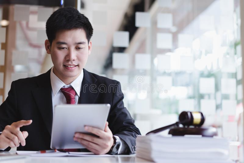 Business lawyers using cell phone for contact customer with brass scale on wooden desk in office. royalty free stock photos