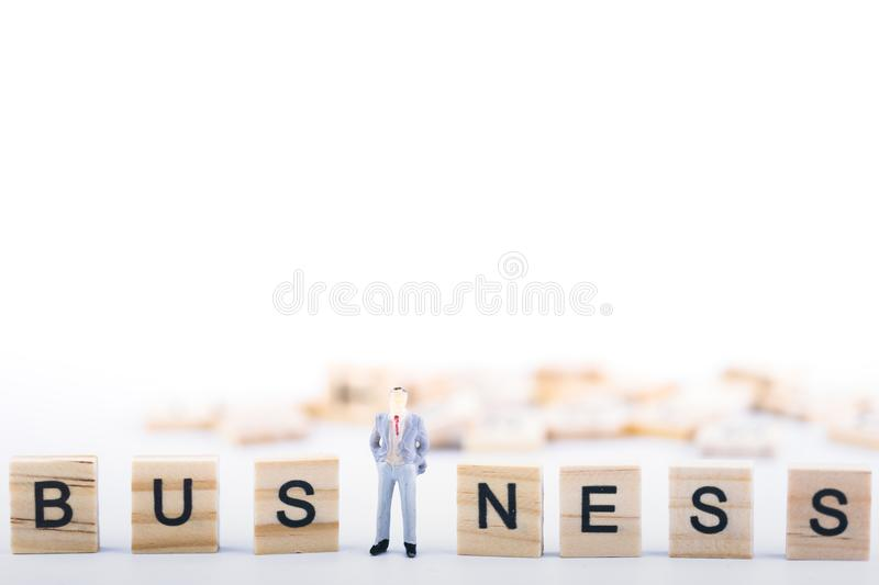 Business leader concept. Miniature people small figure standing in the middle wooden cube with word business on white background. With copy space. Teamwork royalty free stock photo