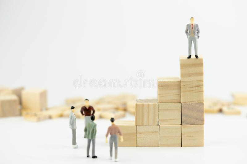 Business leader concept. Miniature people small figure standing in the wood block stacking. With copy space. Teamwork, stock images