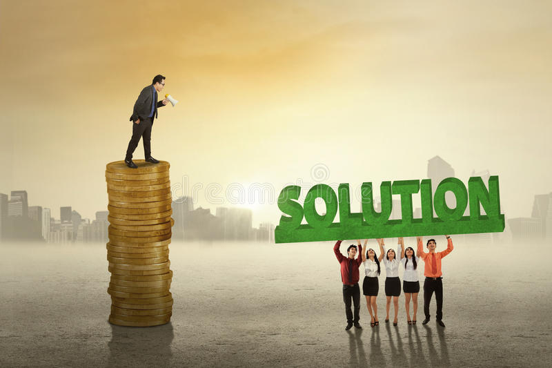 Business leader with employees and solution. Male corporate leader standing on the stack of golden coins while giving command on his employees to bring a royalty free stock photography