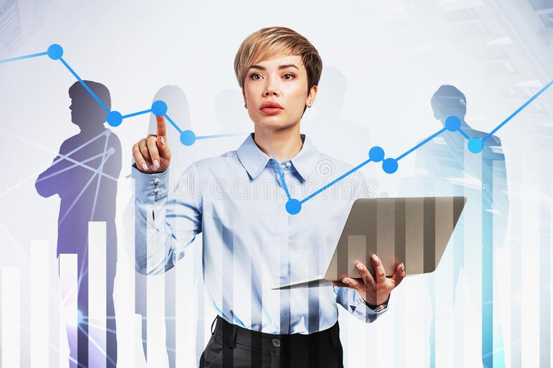 Business leader with laptop, digital charts. Young businesswoman with laptop working with digital graph in city with double exposure of business people stock photo