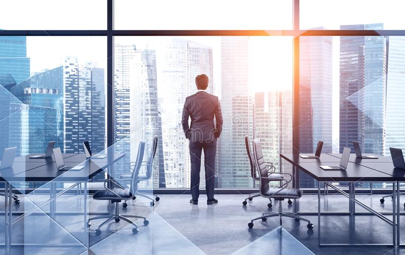 Business leader looking at city, brainstorm. Rear view of businessman looking at city from his panoramic office. Concept of brainstorming and leadership. Toned stock images