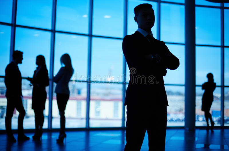 Business leader. Outlines of business team standing against window with leader in front stock image