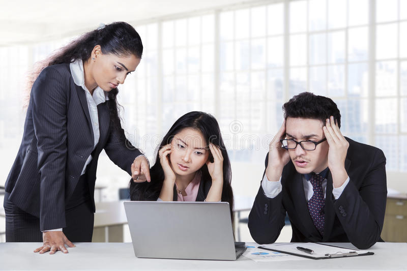 Business leader stressing her employees. Bossy businesswoman pointing at laptop to show the mistake of her employees royalty free stock images