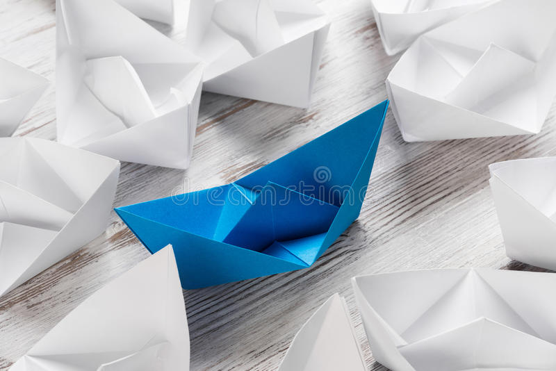 Business leadership concept. Set of origami boats on wooden table royalty free stock photography