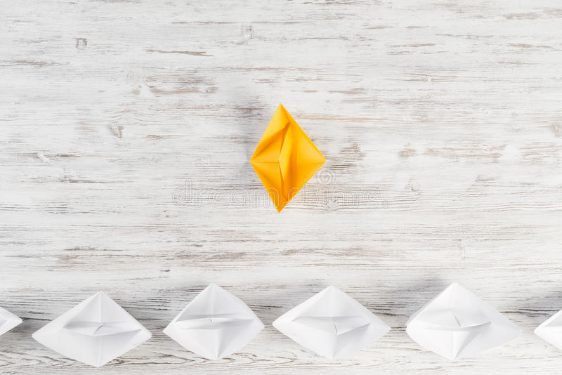 Business leadership concept. Set of origami boats on wooden table stock images