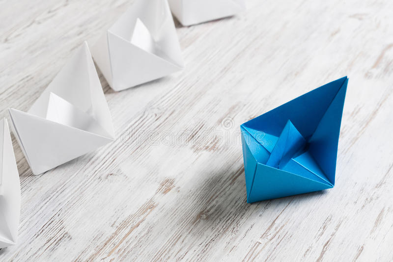 Business leadership concept. Set of origami boats on wooden table royalty free stock image