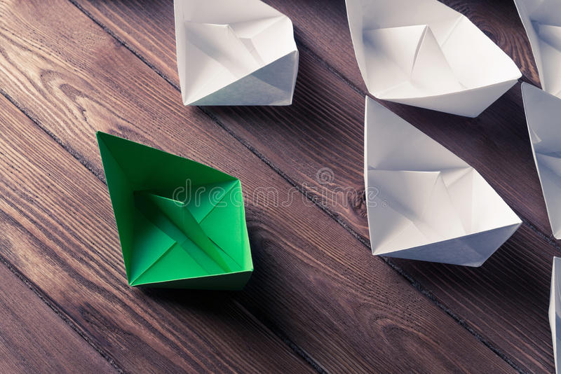 Business leadership concept with white and color paper boats on. Set of origami boats on wooden table stock photo
