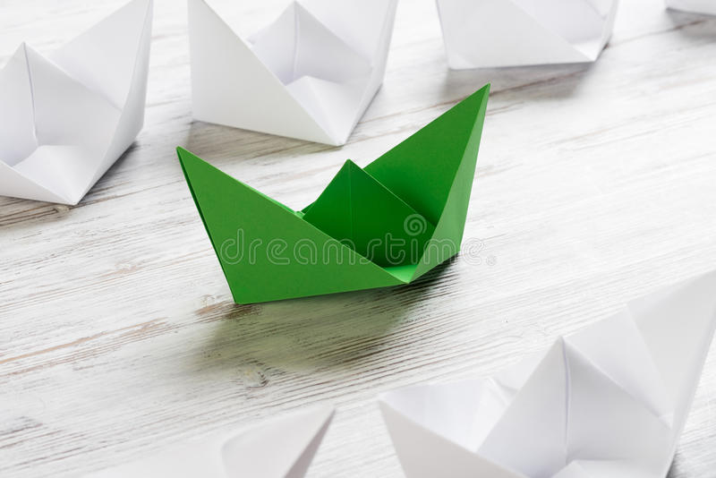 Business leadership concept with white and color paper boats on wooden table. Set of origami boats on wooden table stock photos