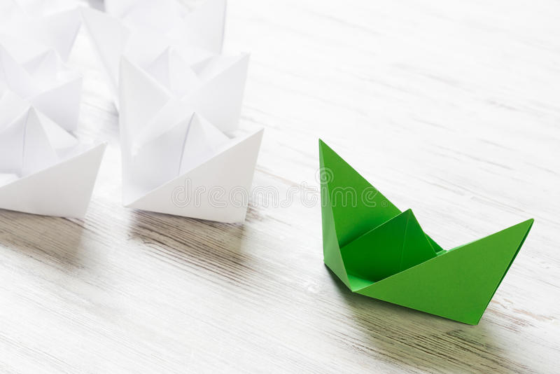 Business leadership concept with white and color paper boats on wooden table. Set of origami boats on wooden table stock photography