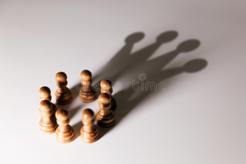 Business leadership, teamwork power and confidence concept. Chess pawns with king shadow stock photo