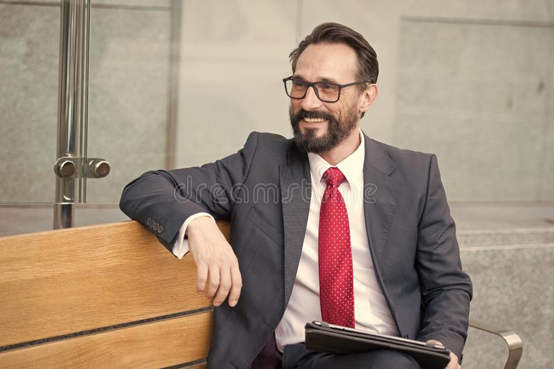 Business, Leisure, technology, communication and people concept-man with tablet on city street bench. Portrait of handsome smiling royalty free stock image