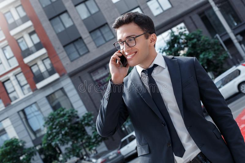Business lifestyle. Businessman in eyeglasses standing on the city street talking on smartphone looking aside cheerful stock images