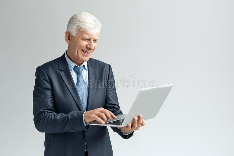 Business Lifestyle. Businessman standing isolated on gray browsing internet on laptop smiling joyful stock photography