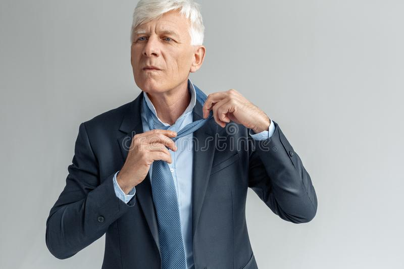 Business Lifestyle. Businessman standing isolated on gray untying tie thoughtful. Senior business man studio standing isolated on gray wall untying tie stock images