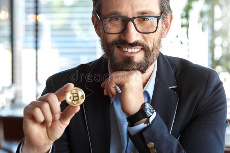 Business Lifestyle. Trader in glasses sitting at cafe with cryptocurrency coin looking camera laughing joyful royalty free stock image