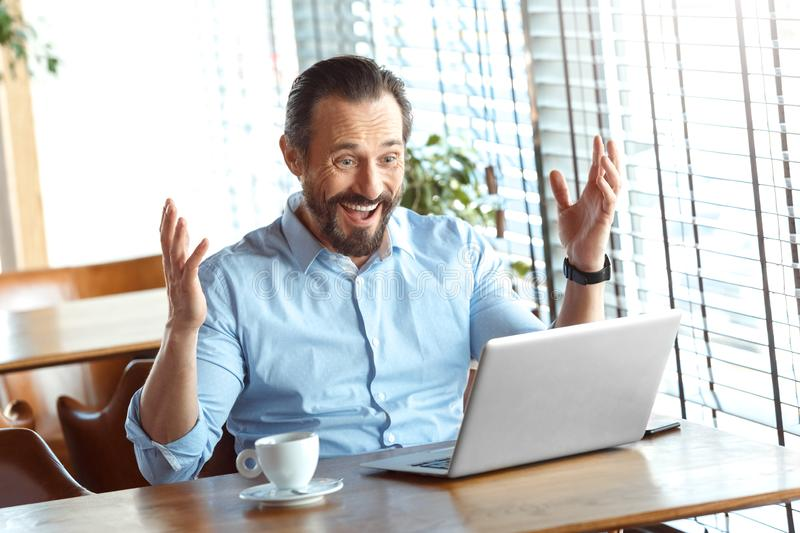 Business Lifestyle. Trader sitting at cafe with coffee looking at laptop hands aside smiling surprised. Mature man trader sitting at table at cafe at daytime royalty free stock images