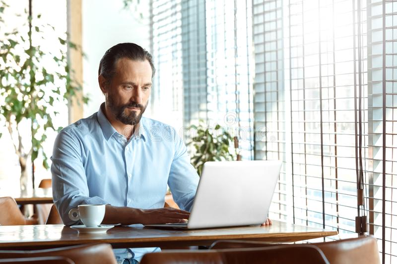 Business Lifestyle. Trader sitting at cafe with coffee working on laptop concentrated. Mature man trader sitting at table at cafe at daytime working concentrated stock image